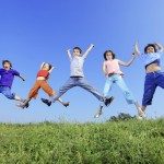 Group of five children jumping on meadow.